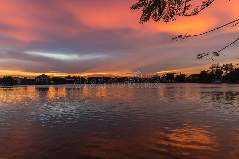 Puesta del sol sobre un lago tranquilo durante verano en Bangkok foto de archivo libre de regalías