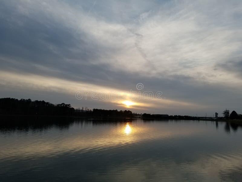 Puesta del sol sobre un lago tranquilo en primavera imágenes de archivo libres de regalías