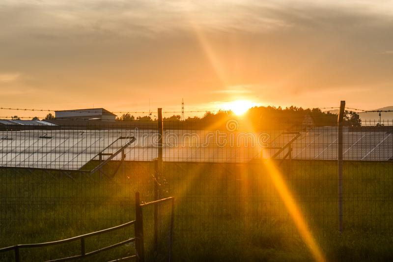 Puesta del sol sobre una central eléctrica fotovoltaica con los módulos fotovoltaicos para la energía renovable en el campo Gener fotos de archivo libres de regalías