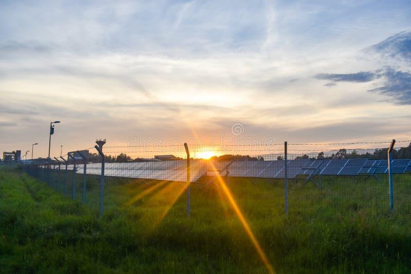 Puesta del sol sobre una central eléctrica fotovoltaica con los módulos fotovoltaicos para la energía renovable en el campo Gener imágenes de archivo libres de regalías