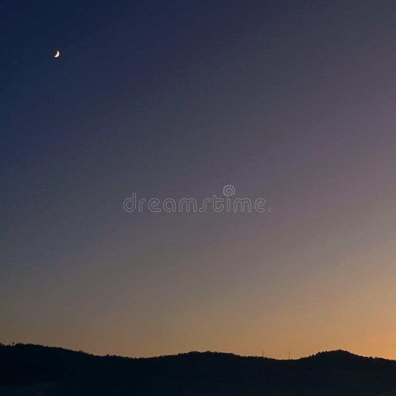 Puesta del sol sobre una colina y la luna que nos pasa por alto imagen de archivo libre de regalías
