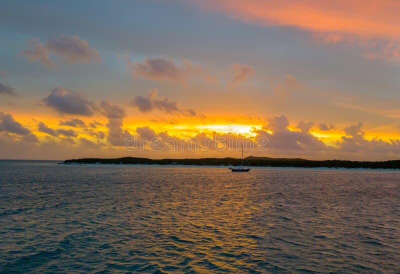 Puesta del sol sobre una isla en Bahamas y una navegación del barco de navegación en el océano foto de archivo libre de regalías