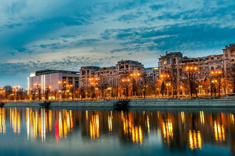 Puesta del sol Splaiul Unirii del paisaje del centro de ciudad de Bucarest en el río de Dambovita de la oscuridad foto de archivo libre de regalías
