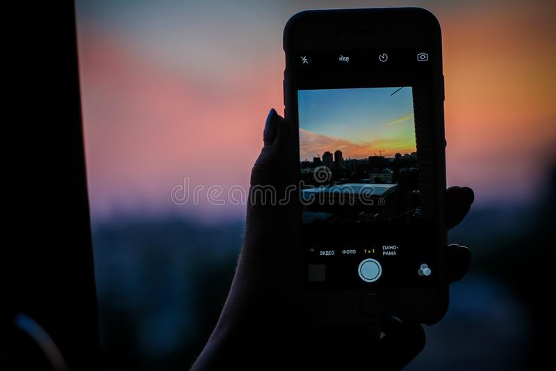 Puesta del sol a través del teléfono imágenes de archivo libres de regalías