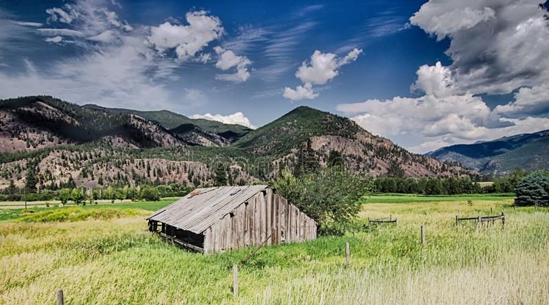 Puesta del sol del verano con un granero rojo en Montana y Rocky Mountai rurales imagenes de archivo