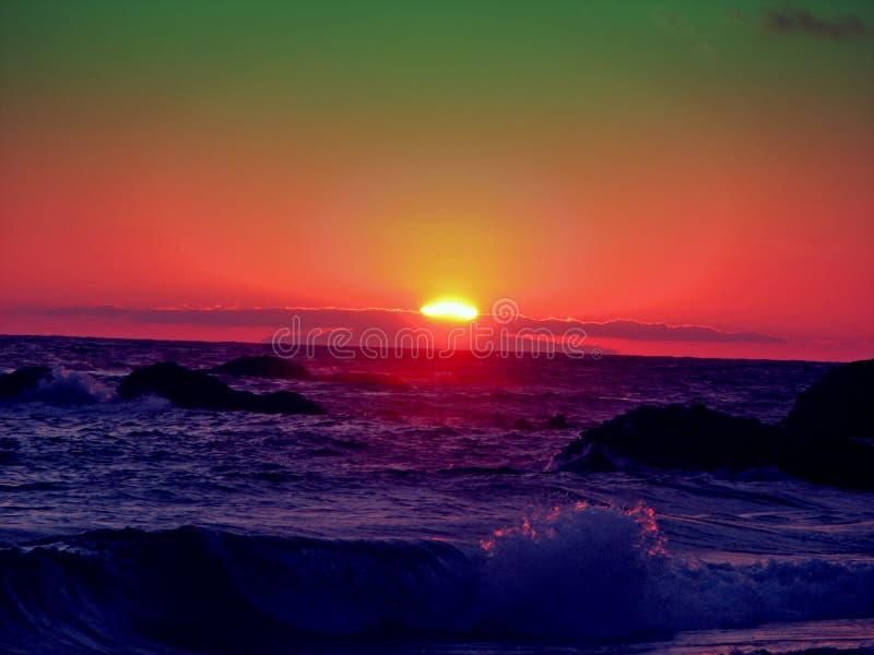 Puesta del sol verde y roja sobre el mar fotos de archivo libres de regalías