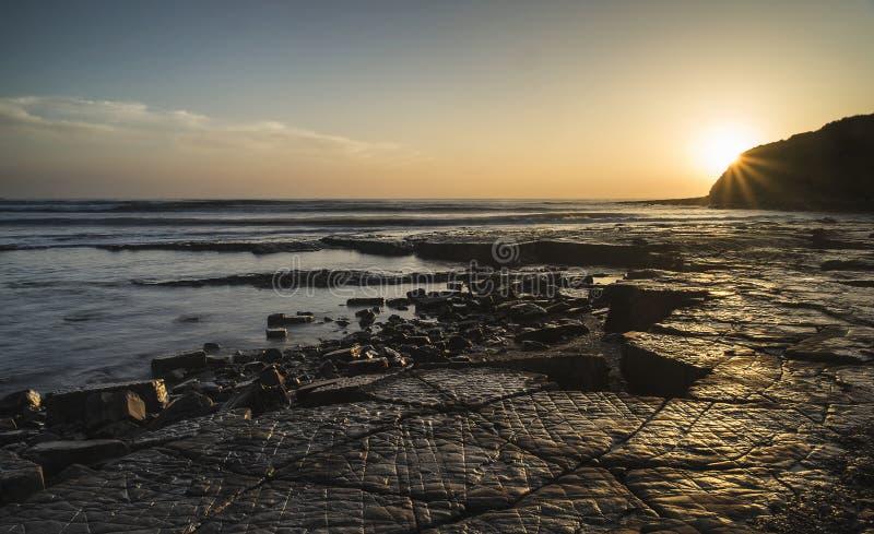 Puesta del sol vibrante de Beautfiul sobre la costa jurásica Inglés de la bahía de Kimmeridge foto de archivo