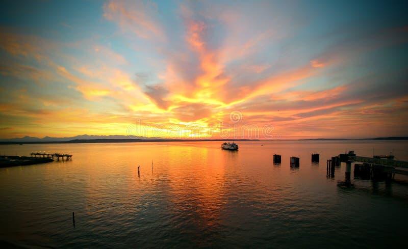 Puesta del sol vibrante en el agua, transbordador que vuelve a casa fotos de archivo