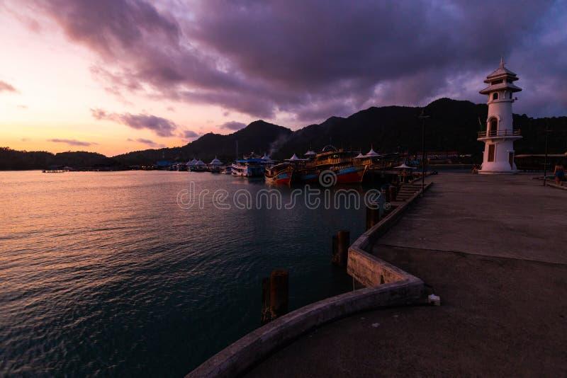 Puesta del sol viva con una opinión sobre una explosión Bao del pueblo de los pescadores populares en la isla de Ko CHang en Tail imagen de archivo
