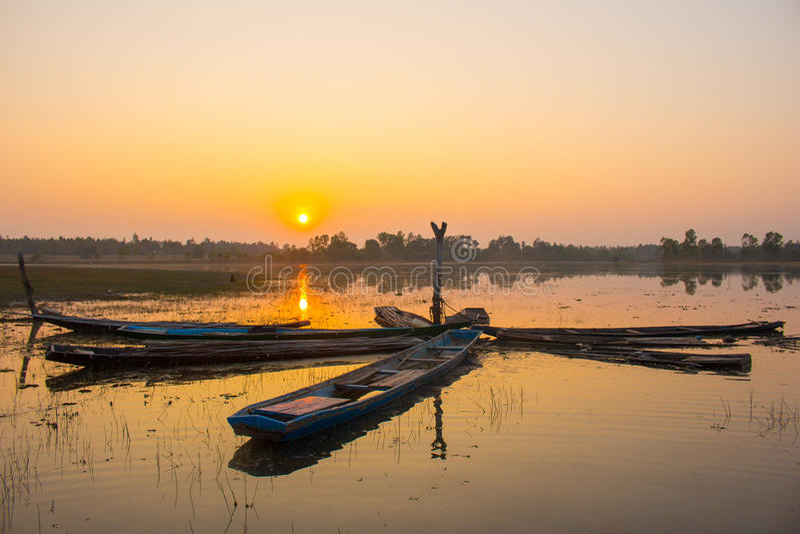 Puesta del sol y barcos de la silueta en el lago fotos de archivo