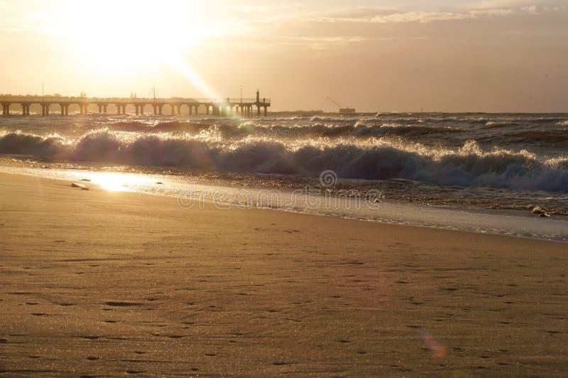 Puesta del sol y embarcadero en el mar Báltico, el viento y la tormenta en el mar imagenes de archivo