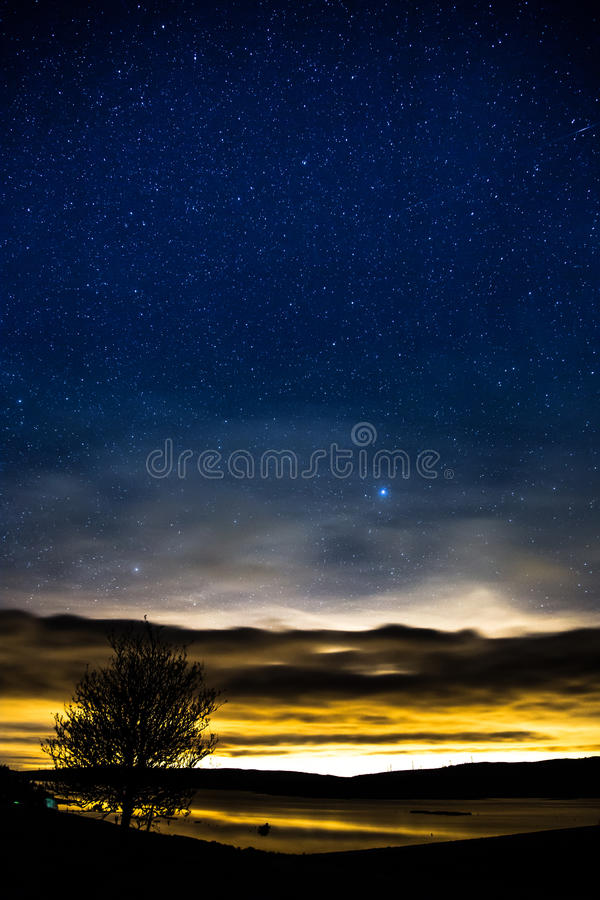 Puesta del sol y estrellas sobre el depósito de Llyn Brenig situado en País de Gales foto de archivo libre de regalías
