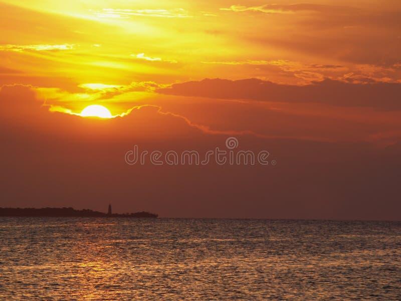 Puesta del sol y faro del mar fotografía de archivo libre de regalías