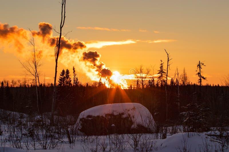 Puesta del sol y humo del paisaje del invierno en el invierno Ontario Canadá foto de archivo libre de regalías