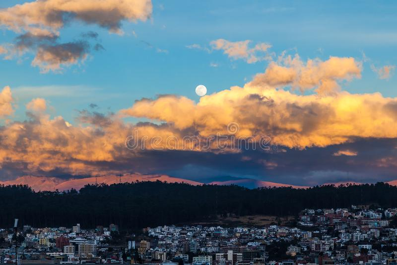 Puesta del sol y la luna sobre ellos, Quito fotografía de archivo