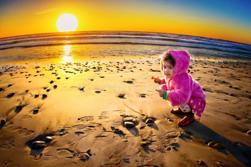 Puesta del sol y niño imagen de archivo