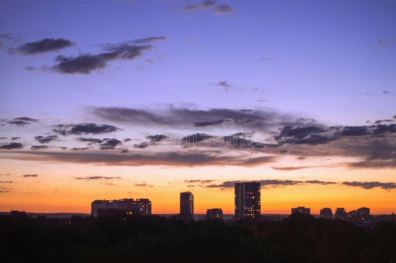 Puesta del sol y nubes bajas en cielo contra fondo del hig urbano fotos de archivo