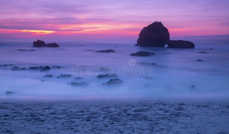Puesta del sol y ondas en la playa en Biarritz fotografía de archivo