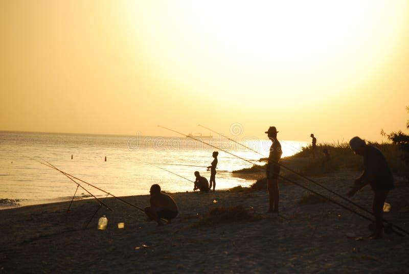 Puesta del sol y pescador foto de archivo libre de regalías