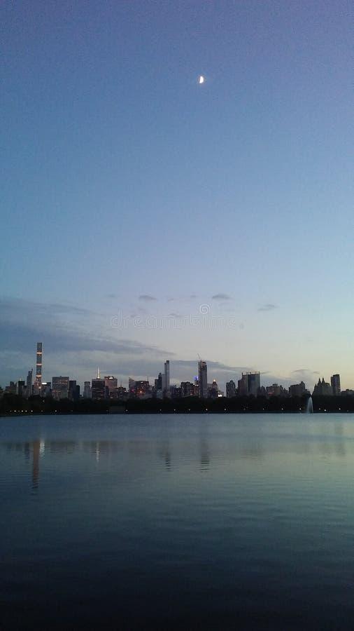 Puesta del sol y salida de la luna sobre el Midtown y los edificios superiores del lado oeste vistos de Central Park en Manhattan fotografía de archivo libre de regalías