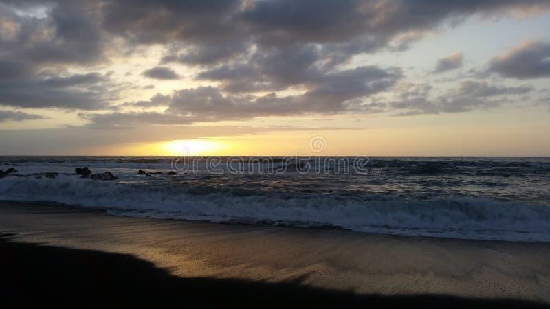 Puestas del sol hermosas en la playa negra 22 de la arena imágenes de archivo libres de regalías