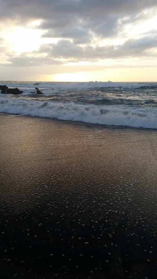 Puestas del sol hermosas en la playa negra 18 de la arena fotografía de archivo