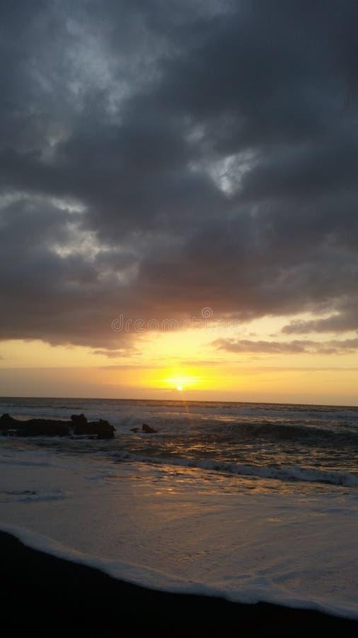 Puestas del sol hermosas en la playa negra 1 de la arena imagen de archivo