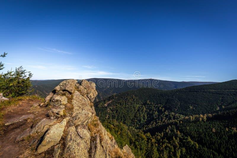 Puesto de observación Rysi skaly con Praded en el fondo, rocas en el primero plano y valle verde por completo de árboles conífero imagenes de archivo