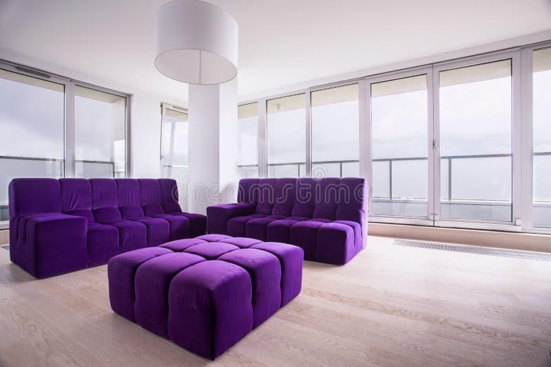 Pufe e sofá violetas fotos de stock