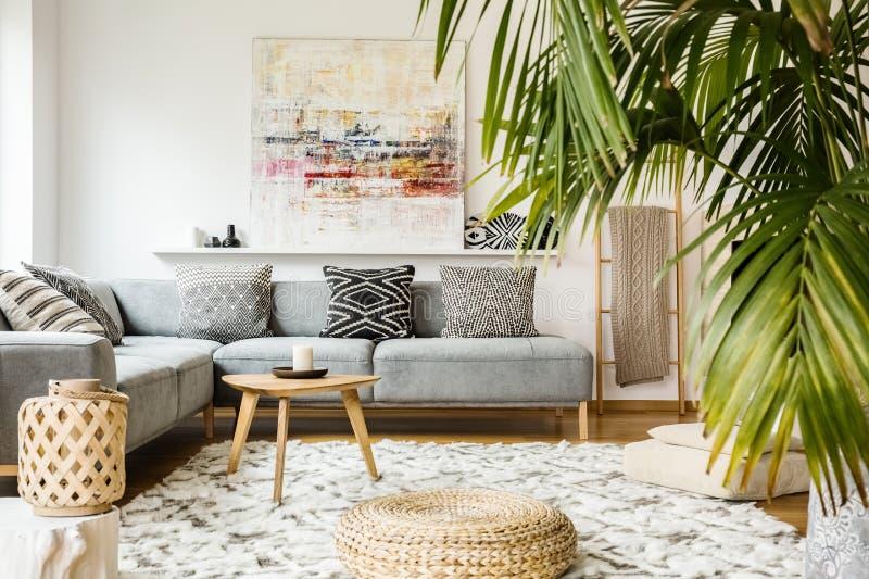Pufe e tabela de madeira na sala de visitas moderna com pintura acima imagens de stock