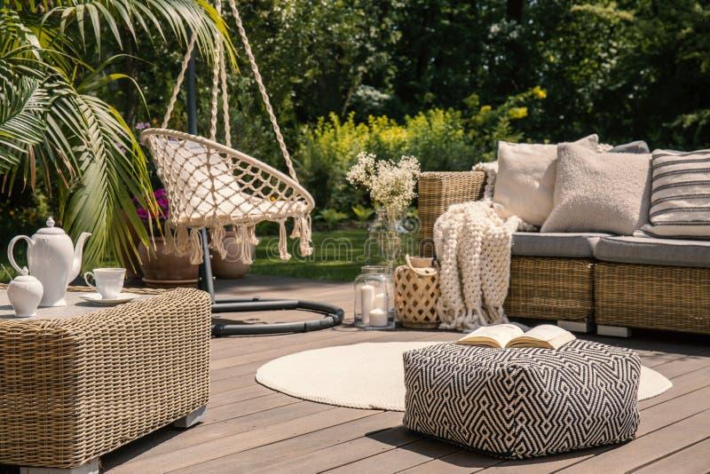 Puff auf hölzerner Terrasse mit Rattansofa und Tabelle im Garten mit hängendem Stuhl Reales Foto stockbilder