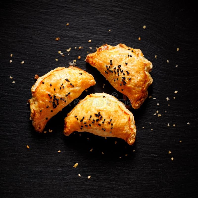 Puff bakverk med svampfyllning sprinklad med nigella-frön på en svart bakgrund, översiktlig royaltyfria bilder
