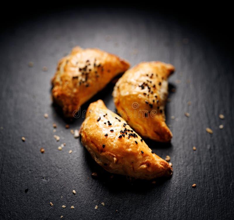 Puff bakverk med svampfyllning sprinklad med nigella-frön på en svart bakgrund, översiktlig royaltyfri foto