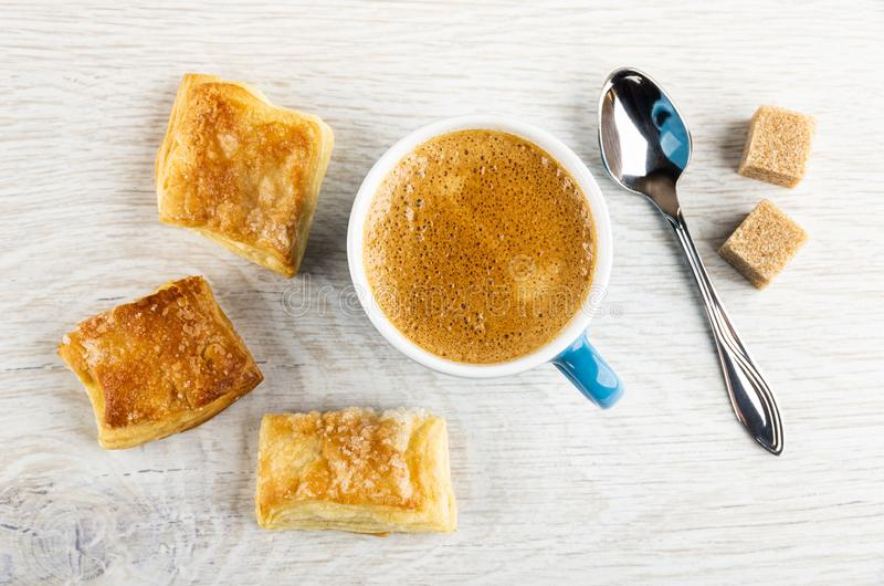 Puff cookies with sugar, cup with coffee, spoon, sugar on wooden table. Top view. Small puff cookies with sugar, blue cup with coffee espresso, spoon, sugar stock photos