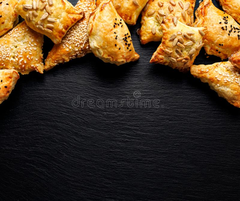 Puff-konditorivaror med olika fyllningar som strös ut med frön Franska bakverk fyllda med svamp, spenat och ost på svart rygg royaltyfria bilder
