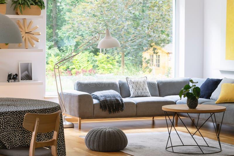 Puff nahe bei Tabelle im modernen Wohnzimmerinnenraum mit grauem Mais lizenzfreie stockfotos
