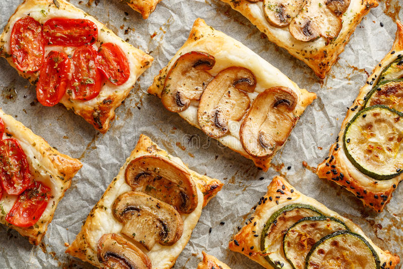 Puff pastry appetizers with vegetables; mushrooms, tomatoes and zucchini royalty free stock photo