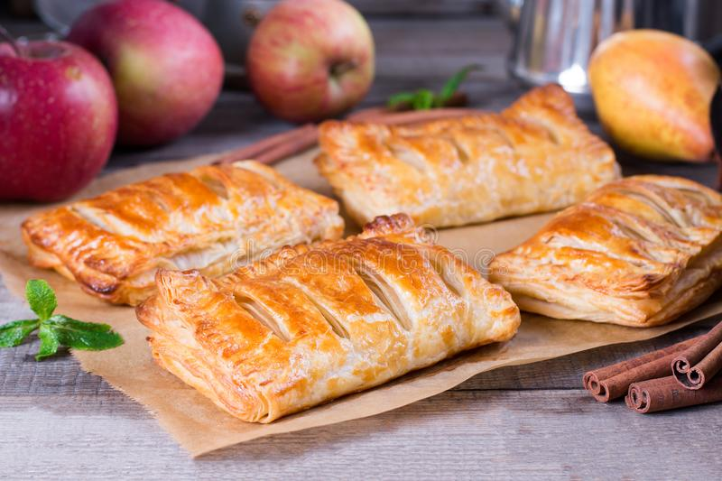 Puff pastry apple pastry turnovers for dessert. On a wooden table royalty free stock photos