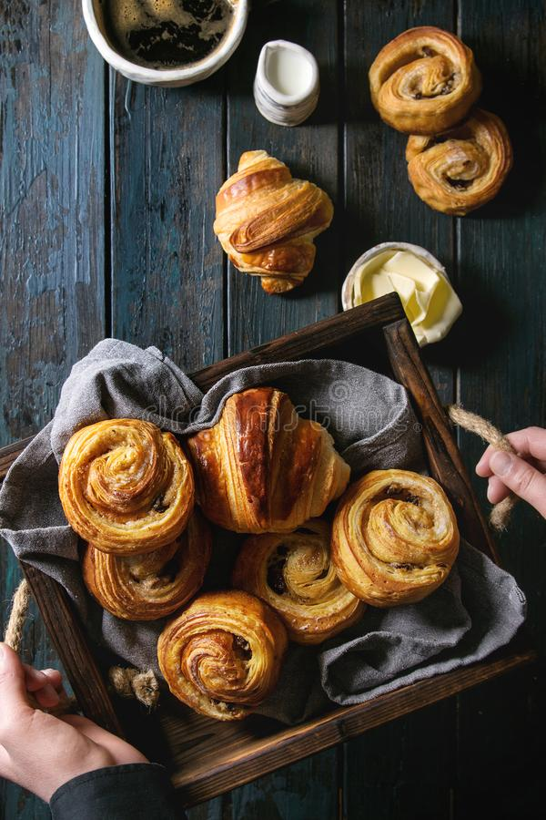 Puff pastry buns. Child holding in hands tray with variety of homemade puff pastry buns cinnamon rolls and croissant. Coffee cup, jam, butter as breakfast over stock photography