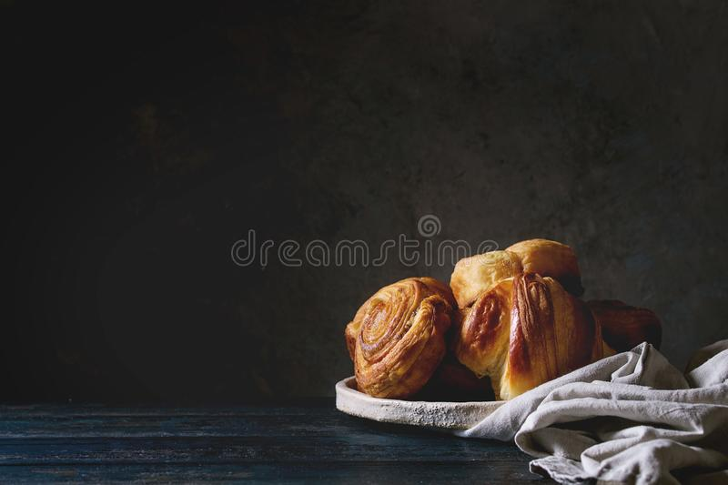 Puff pastry buns. Variety of homemade puff pastry buns cinnamon rolls and croissant in ceramic plate on wooden table. Dark still life. Copy space royalty free stock photos