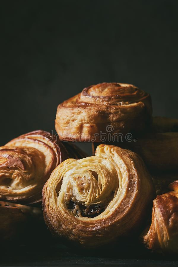 Puff pastry buns. Variety of homemade puff pastry buns cinnamon rolls and croissant. Dark still life. Close up stock photography