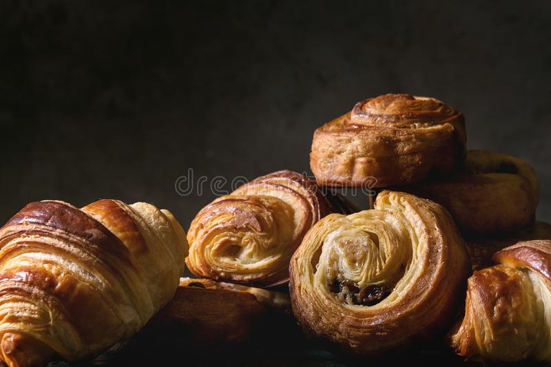 Puff pastry buns. Variety of homemade puff pastry buns cinnamon rolls and croissant. Dark still life. Close up stock photo