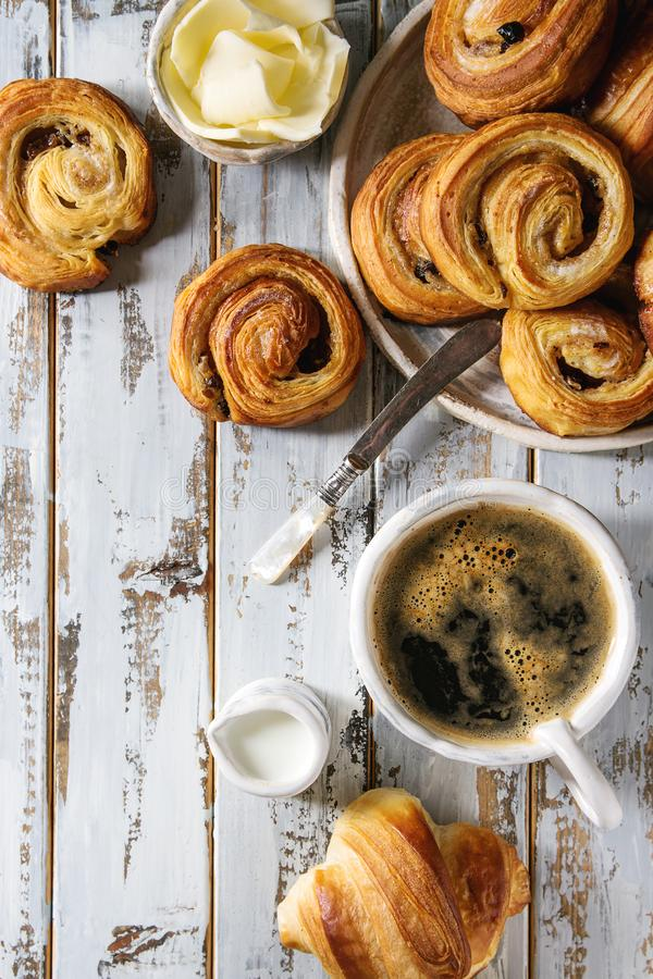 Puff pastry buns. Variety of homemade puff pastry buns cinnamon rolls and croissant served with coffee cup, jam, butter as breakfast over white plank wooden royalty free stock images