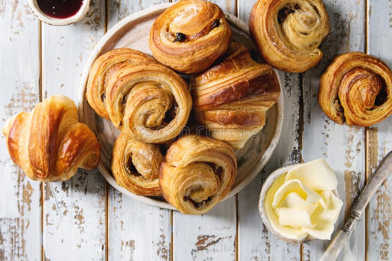 Puff pastry buns. Variety of homemade puff pastry buns cinnamon rolls and croissant served with jam, butter as breakfast over white plank wooden background. Flat stock images