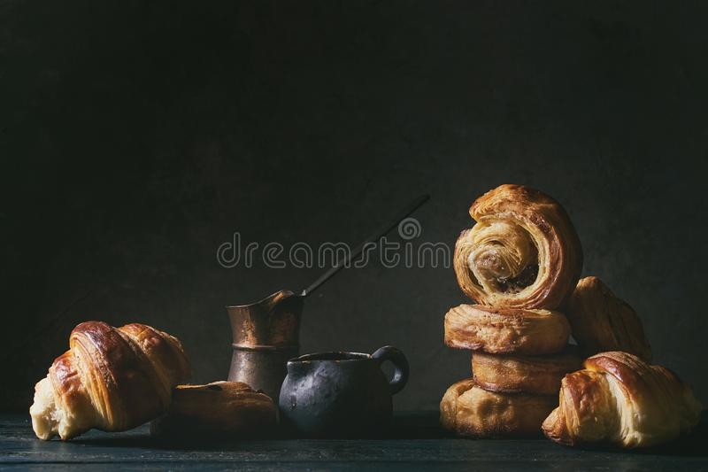 Puff pastry buns. Variety of homemade puff pastry buns cinnamon rolls and croissant served with vintage coffee pot on wooden table. Dark still life. Copy space royalty free stock photo