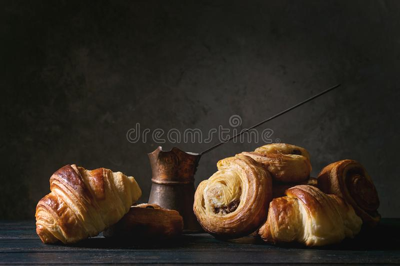 Puff pastry buns. Variety of homemade puff pastry buns cinnamon rolls and croissant served with vintage coffee pot on wooden table. Dark still life. Copy space royalty free stock image
