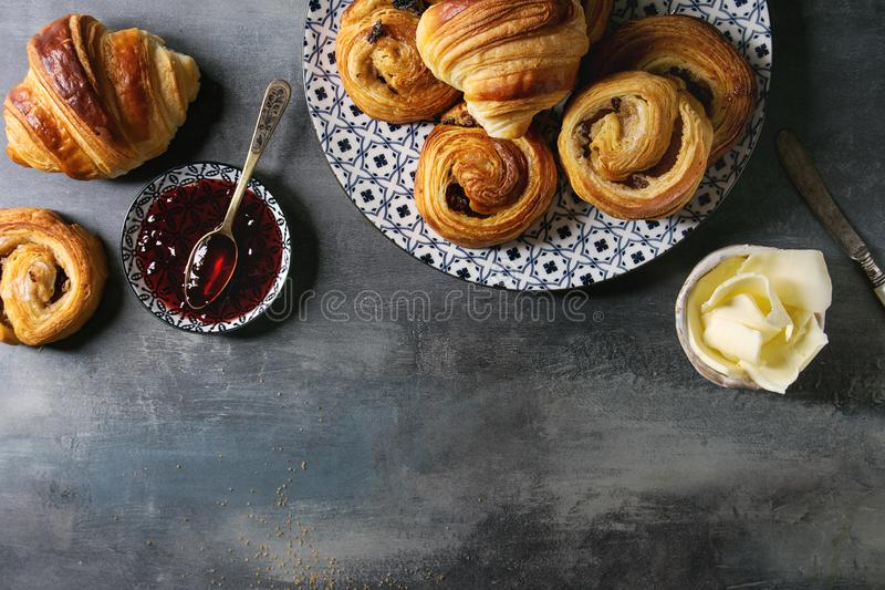 Puff pastry buns. Variety of homemade puff pastry buns cinnamon rolls and croissant served with jam, butter as breakfast over blue texture background. Flat lay royalty free stock photos