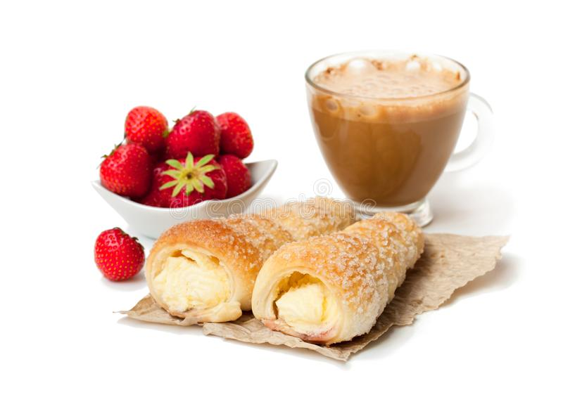 Puff pastry horns with cup of cappuccino and strawberry isolate royalty free stock photography