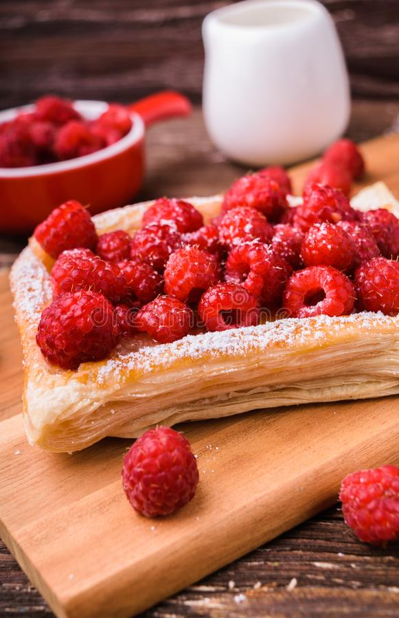 Puff pastry with raspberries. Homemade puff pastry with raspberries. Sweet tasty dessert. decorated with powdered sugar. On wooden cooking board. Baking concept stock photos