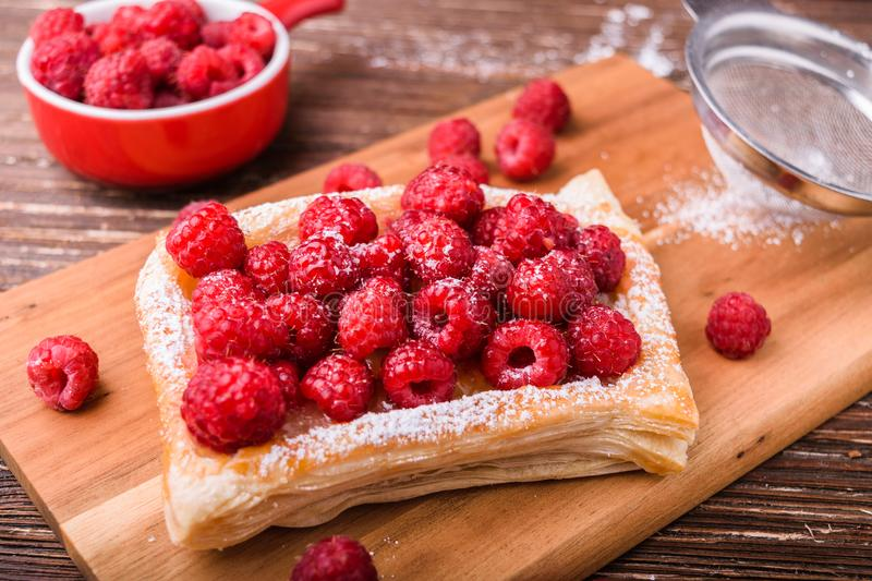 Puff pastry with raspberries. Homemade puff pastry with raspberries. Sweet tasty dessert. decorated with powdered sugar. On wooden cooking board. Baking concept royalty free stock images